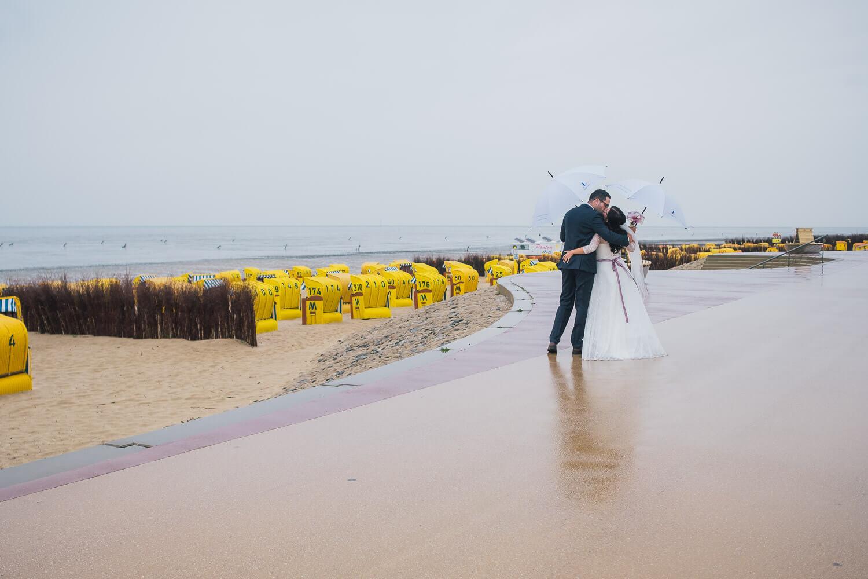 Hochzeitsfotos Sahlenburg mit Brautpaar und Regenschirmen